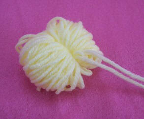 Tie yarn around loops to make a pompom