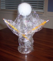 Cover a recycled water bottle with plastic wrap to craft a ghost