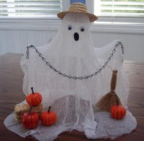 Make a Halloween ghost from cheesecloth and dress him in a straw hat.