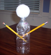 Recycled water bottle makes a mold for a ghost made of cheesecloth.